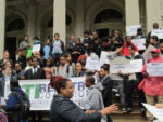 Members of the New York ATI/Reentry Coalition rally on the steps of City Hall.