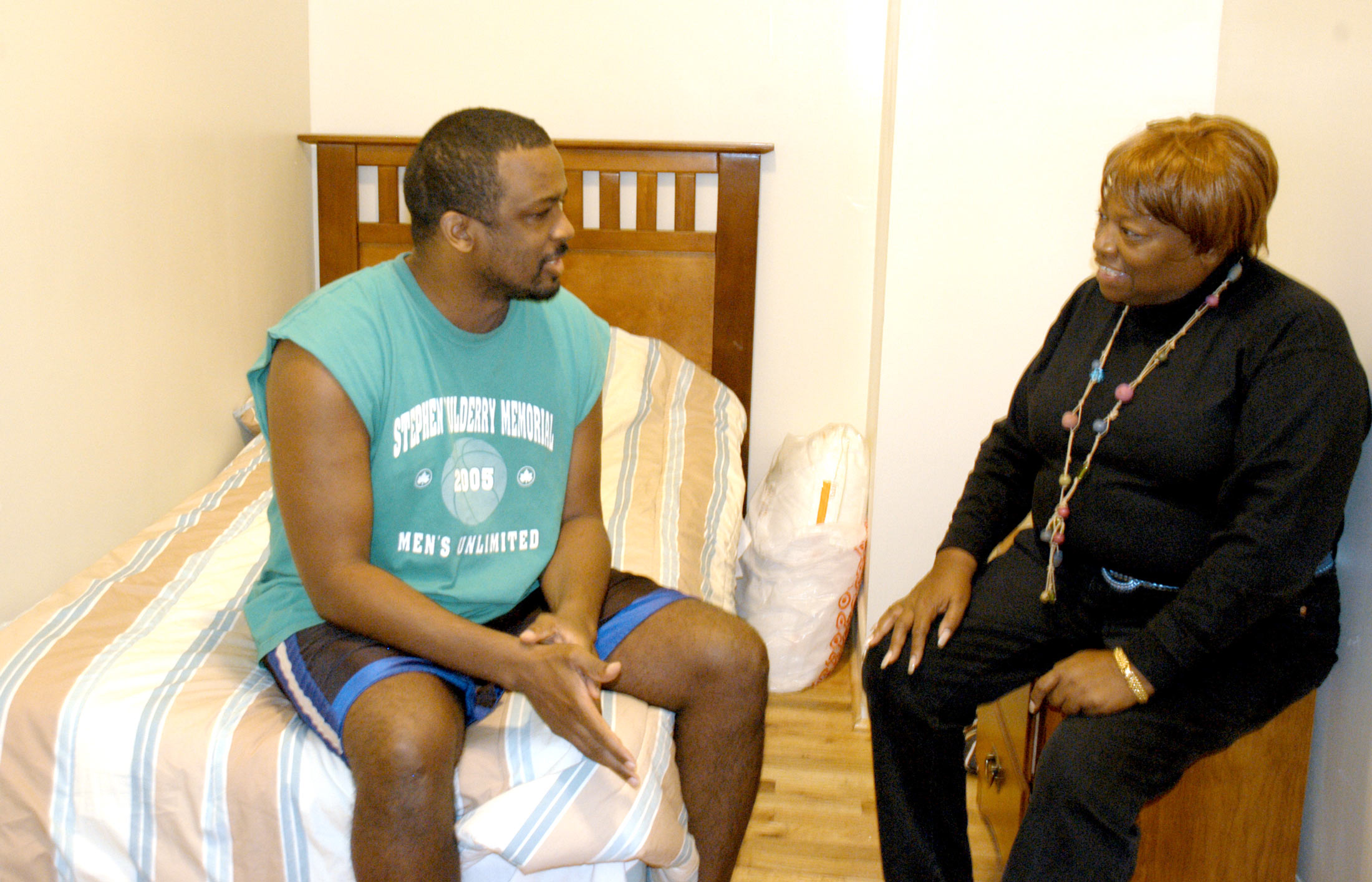 A CASES counselor visits with a participant in his bedroom